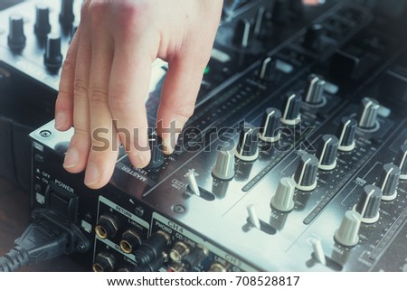 Hand adjusting audio mixer on concert and sound record