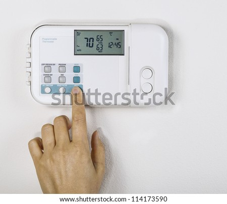 Hand adjusting inside home temperature to seventy degrees fahrenheit with White wall as background