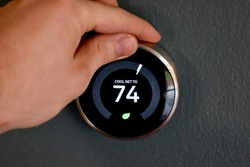 Hand adjusting temperature on smart thermostat to save energy and money. Green tech!