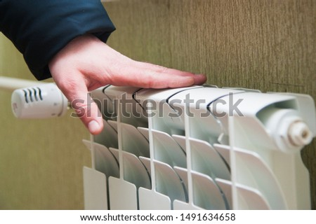 Hand adjusting the knob of heating radiator. Heating in the house