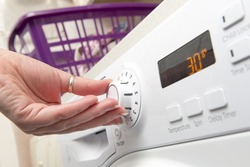 Hand adjusting the temperature setting of a clothes dryer by turning a knob