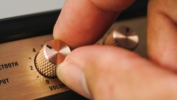 Hand adjusting volume control.Use hand to adjust the volume at the volume control button of the amplifier.
