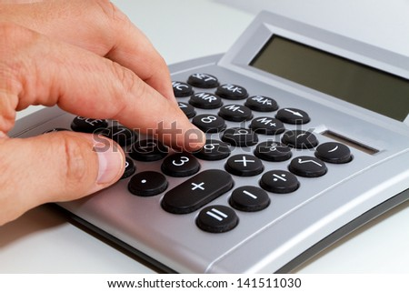 Hand and calculator