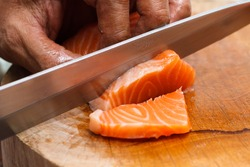 Hand and fingers Japanese chef use sharp knife slicing fresh salmon for sashimi sushi. Japanese  traditional food style for good health.