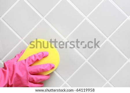 Hand and glove cleaning the bathroom tiles.