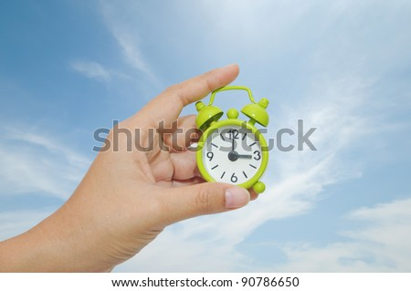 Hand and Green Alarm Clock