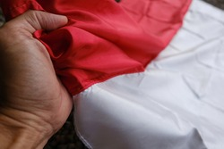Hand and national Indonesia Flag Red and White (Bendera Merah Putih). Indonesian Independence Day, 17 August. Kemerdekaan Republik Indonesia.