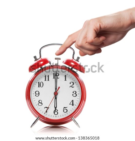 hand and red old style alarm clock isolated on white