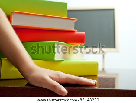 Hand and stack of colored book on the table