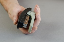 Hand and stapler on gray background. A man holding a plastic paper stapler. Part of a series. Close-up. Selective focus.