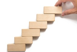 Hand aranging wood block stacking as step stair can use for presentation template or bullet or infographics.