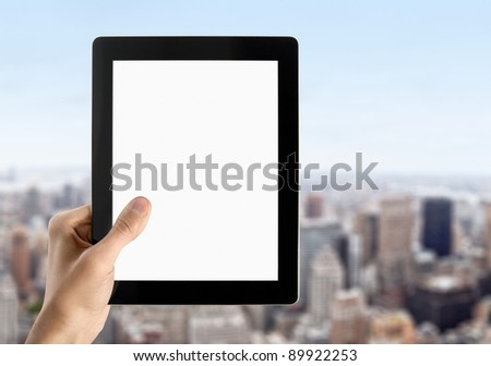 Hand are holding blank digital black frame. Blurred cityscape with skyscrapers on background with blue sky.