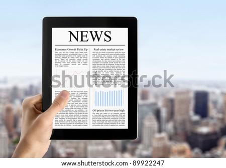Hand are holding digital tablet pc  with fresh news. Blurred cityscape with skyscrapers on background.