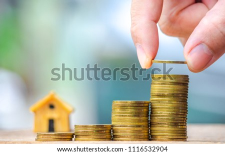 Hand are stacking with coins to save the money invest for the future. Concept for loan, property ladder, financial, mortgage, real estate investment, taxes and bonus. #1116532904