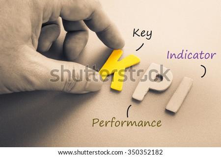 Hand arrange wood letters as KPI acronym (Key Performance Indicator)