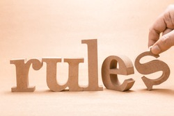 Hand arrange wood letters on brown paper as RULES word