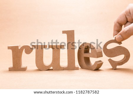 Hand arrange wood letters on brown paper as RULES word #1182787582