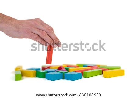 Hand arranging building blocks against white background #630108650