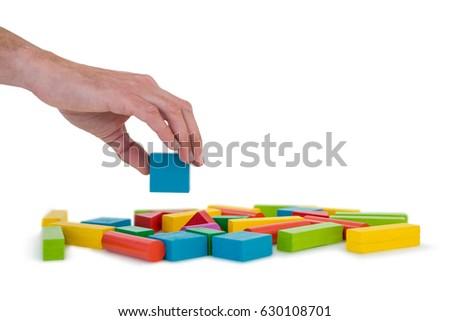 Hand arranging building blocks against white background #630108701