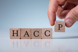 Hand Arranging HACCP Wooden Blocks On Table