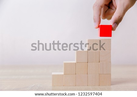 Hand arranging red wood block stacking as step stair,With the concept of a thriving business going for success. #1232597404