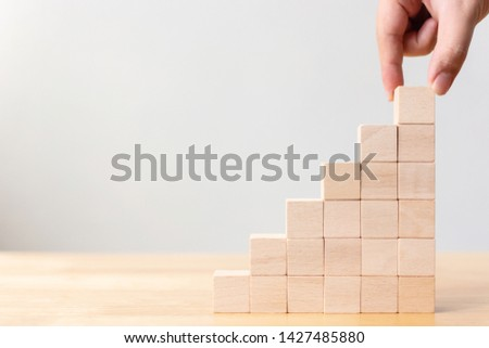 Hand arranging wood block stacking as step stair. Ladder career path concept for business growth success process #1427485880