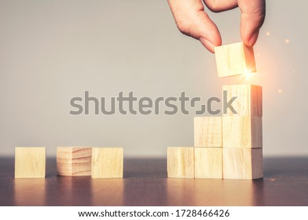 Hand arranging wood block stacking as step stair on table.New normal Business development Decide and choose, Business concept for growth success process,Vintage tone.Copy space Stock foto ©