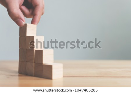 Hand arranging wood block stacking as step stair on wooden table. Business concept for growth success process. Copy space #1049405285