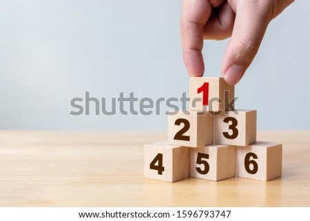 Hand arranging wood block stacking as step stair with number. The best excellent business services rating customer experience concept