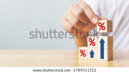 Hand arranging wood block stacking as step stair with sign percent and arrow up symbol. Interest rate financial and mortgage rates concept