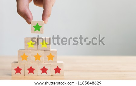 Hand arranging wood block stacking with icon five star symbol. Rating customer service satisfaction experience concept #1185848629