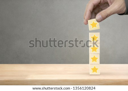 Hand arranging wood block stacking with icon five star symbol. Rating customer service satisfaction experience concept #1356120824