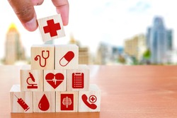 Hand arranging wood block stacking with icon healthcare medical on wooden table against blurred building background , Medical health-care and Insurance for your health concept.