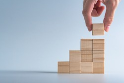 hand arranging wood cube stacking as stair step shape, mock up for create symbol or logo, business growth and management concept