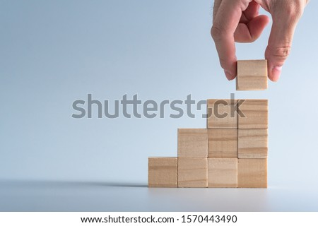 Photo of  hand arranging wood cube stacking as stair step shape, mock up for create symbol or logo, business growth and management concept