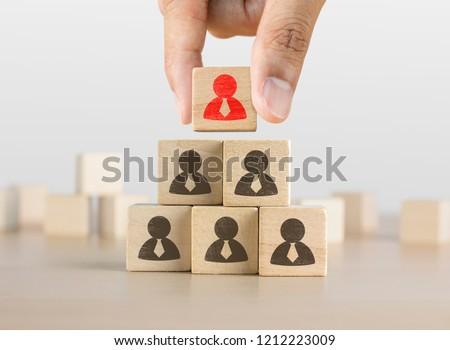 Hand arranging wooden blocks stacking as a pyramid staircase on white background. Leadership, Human resources management, recruitment or corporate hierarchy concept.
