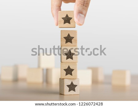 Hand arranging wooden blocks with the five star symbol. The best rating, the best ranking, the best service, goal, success concept. #1226072428