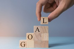 Hand arranging wooden cube with word GOAL stacking as stair step shape. Concept of achieving goal, success, winner, victory or top ranking. Selective focus with depth of field