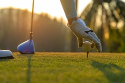 Hand asian woman putting golf ball on tee with club in golf course outdoors on evening and sunset time for healthy power women sport.  Lifestyle Concept