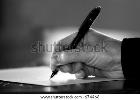Hand at desk signing paperwork/document/contract or making notes - Black and White image.