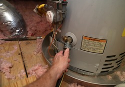 Hand attaches hose to a home water heater to perform maintenance