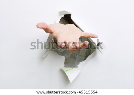 Hand begging through a hole in a paper.