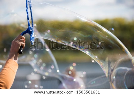 Hand blows soap bubbles.Huge bubble on the street #1505581631