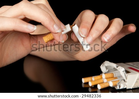 Hand breaking the last cigarette to stop smoking