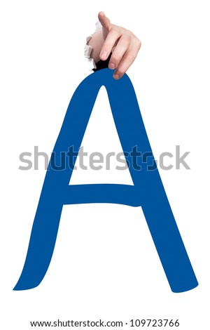 Hand breaking white paper surface holding letter 'A' from alphabet set