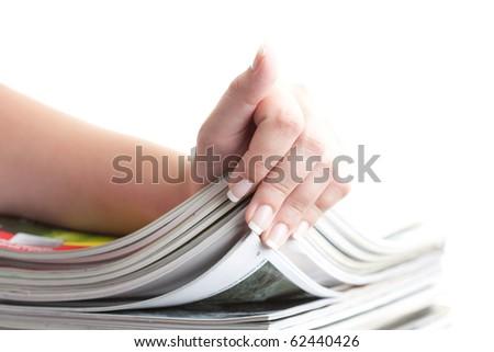 hand browsing through stack of magazines