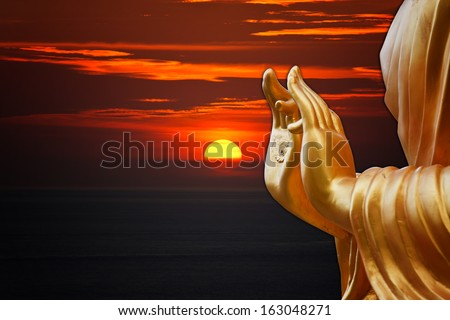hand Buddha statue with sunset sky background