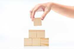 Hand build a pyramid from a wooden block isolated over white background