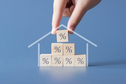 Hand building a house by wooden cubics with the percentage sign on them.Concept of Interest rate financial  mortgage rates,home loans,home refinance.
