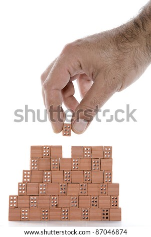 hand building a small brick wall on a white background
